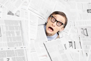 Frightened man emerging from pile of newspapers
