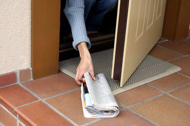 Homeowner grabbing newspaper off front porch