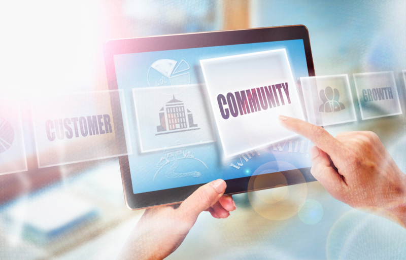 Individual using a tablet and clicking on an icon that says community to support a cause
